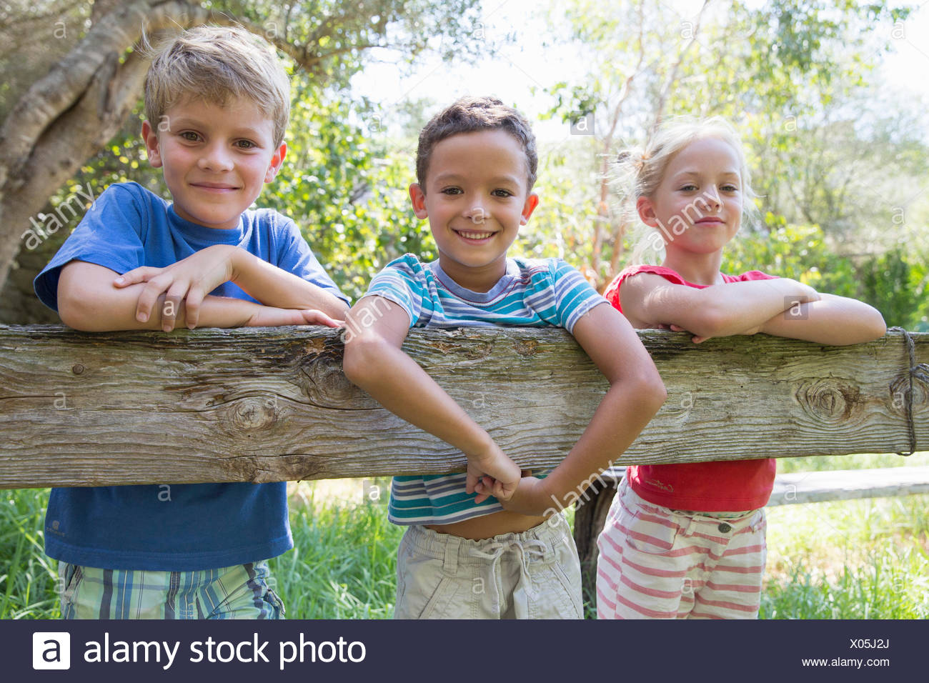 Three children in leaning over garden fence - Stock Image