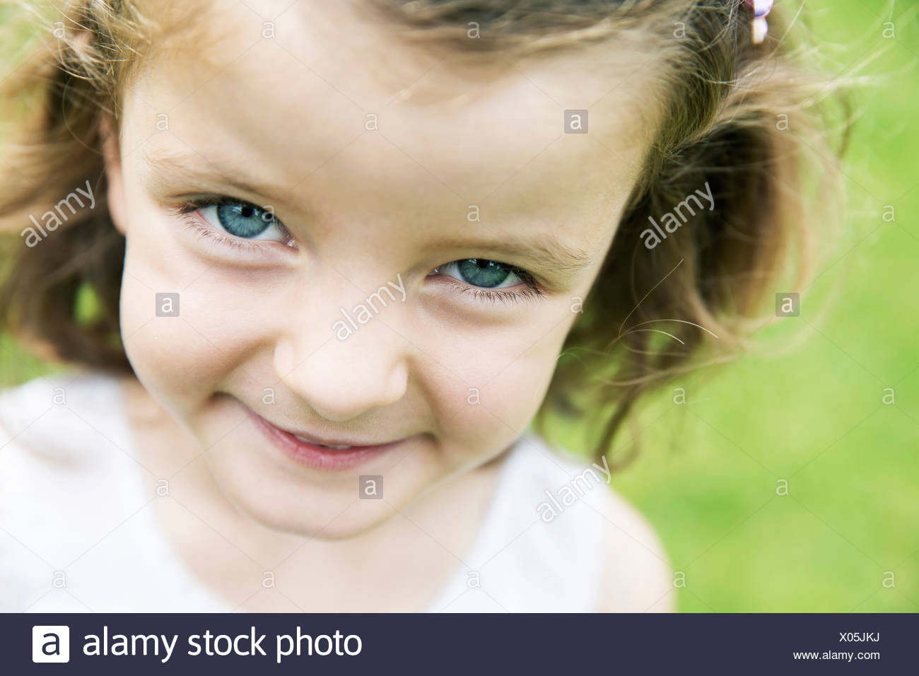 Smiling little girl with blue eyes watching at camera - Stock Image