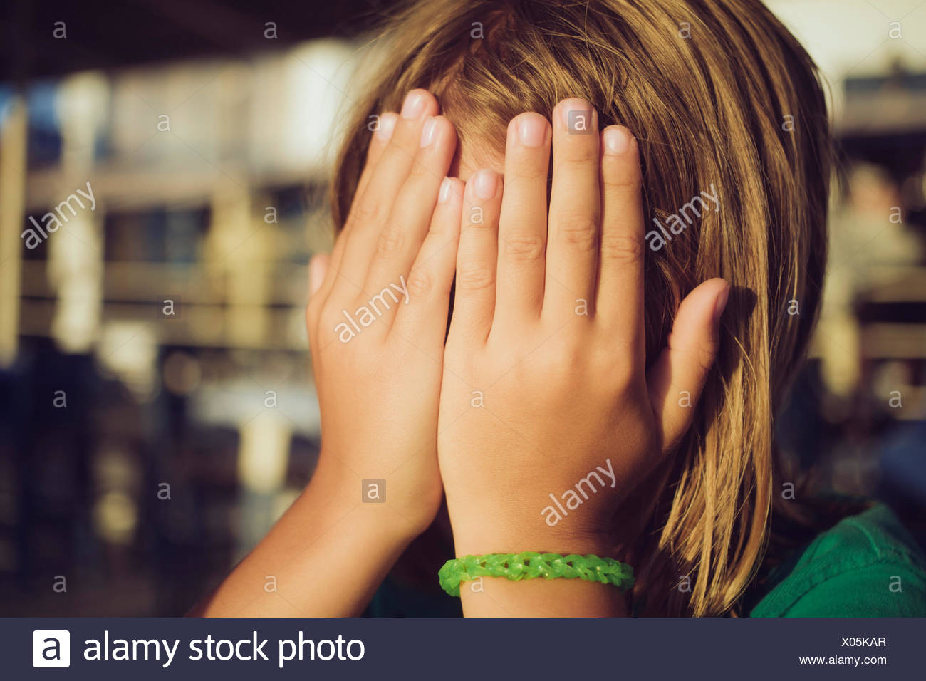 Boy hiding face with hands - Stock Image
