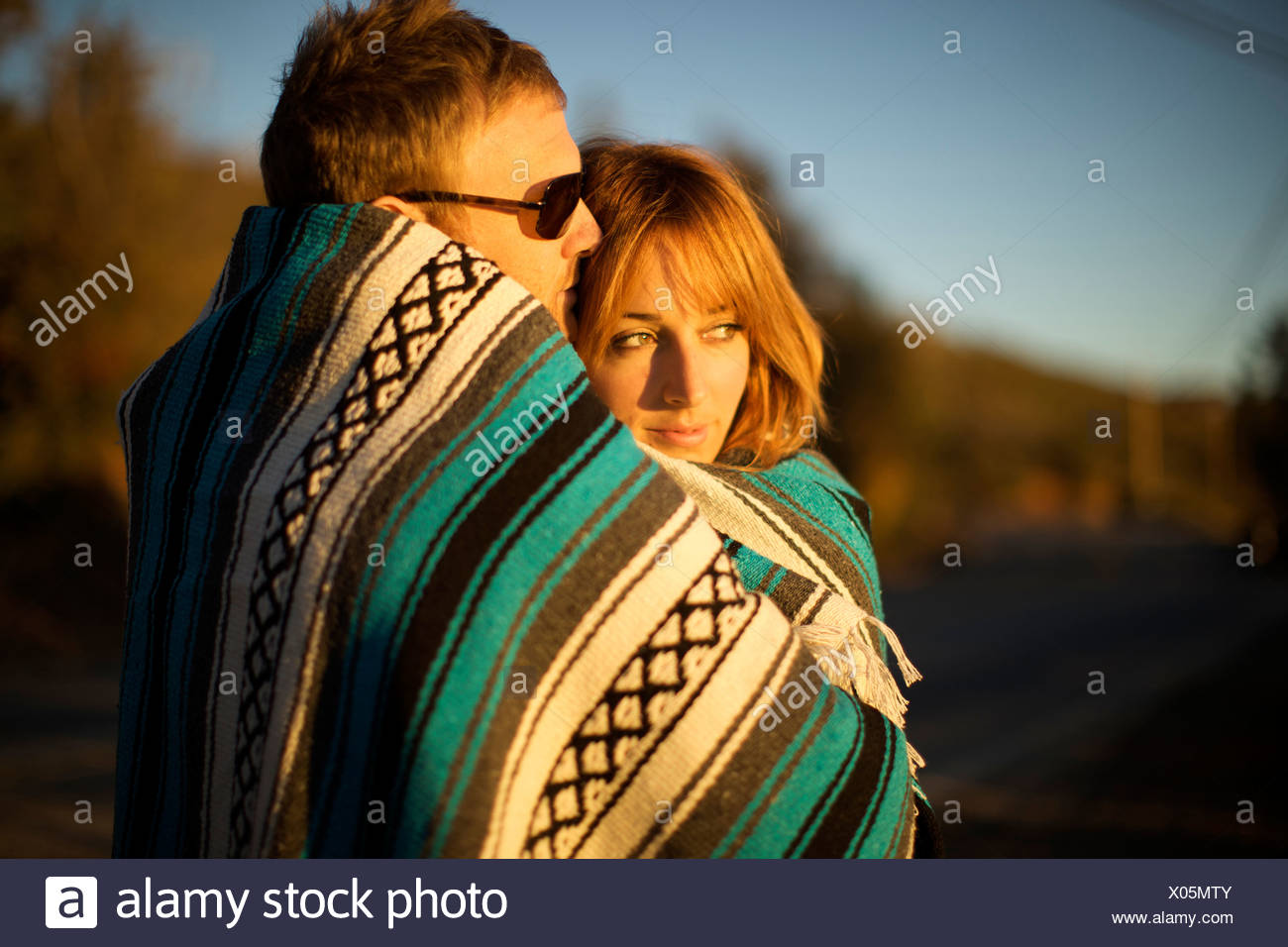Couple wraps themselves in a blue and white blanket and watch the sunset. - Stock Image