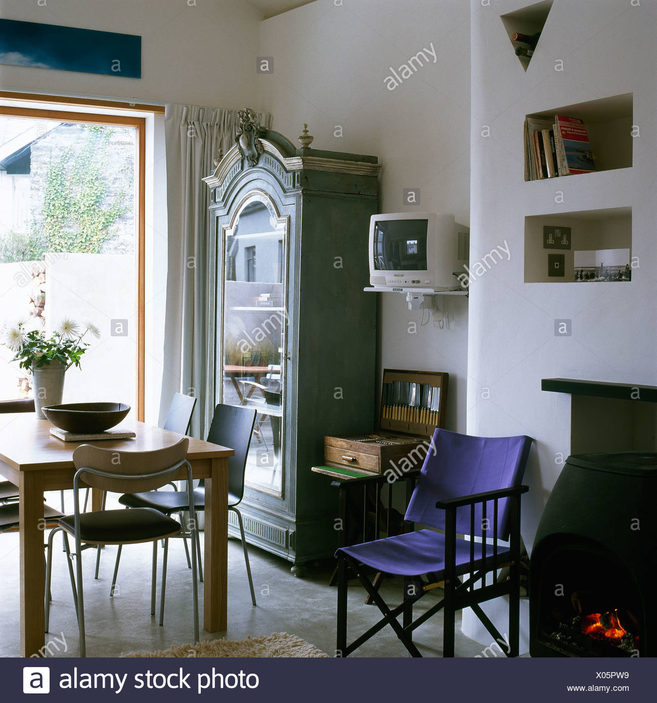 Purple Directoru0027s Chair Beside Wood Burning Stove In Modern Dining Room  With Wall Mounted Television Beside Painted Cupboard
