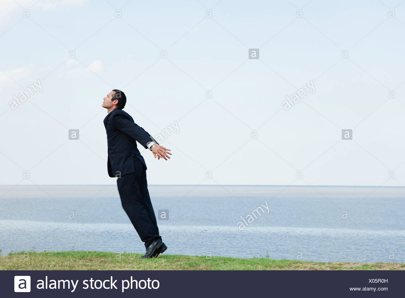 Businessman standing on tiptoe by sea, taking deep breath - Stock Image