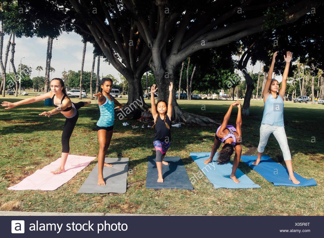 Girls and teenage schoolgirls practicing yoga warrior pose on school playing field - Stock Image