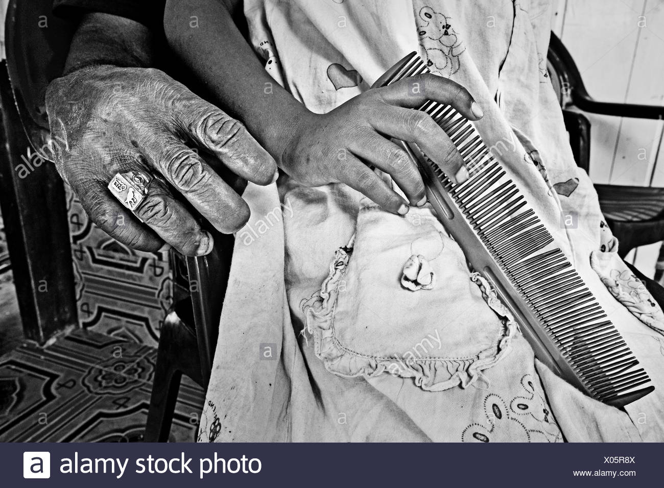 A young child held by her grandfather who is missing fingers from illegal bomb fishing. - Stock Image