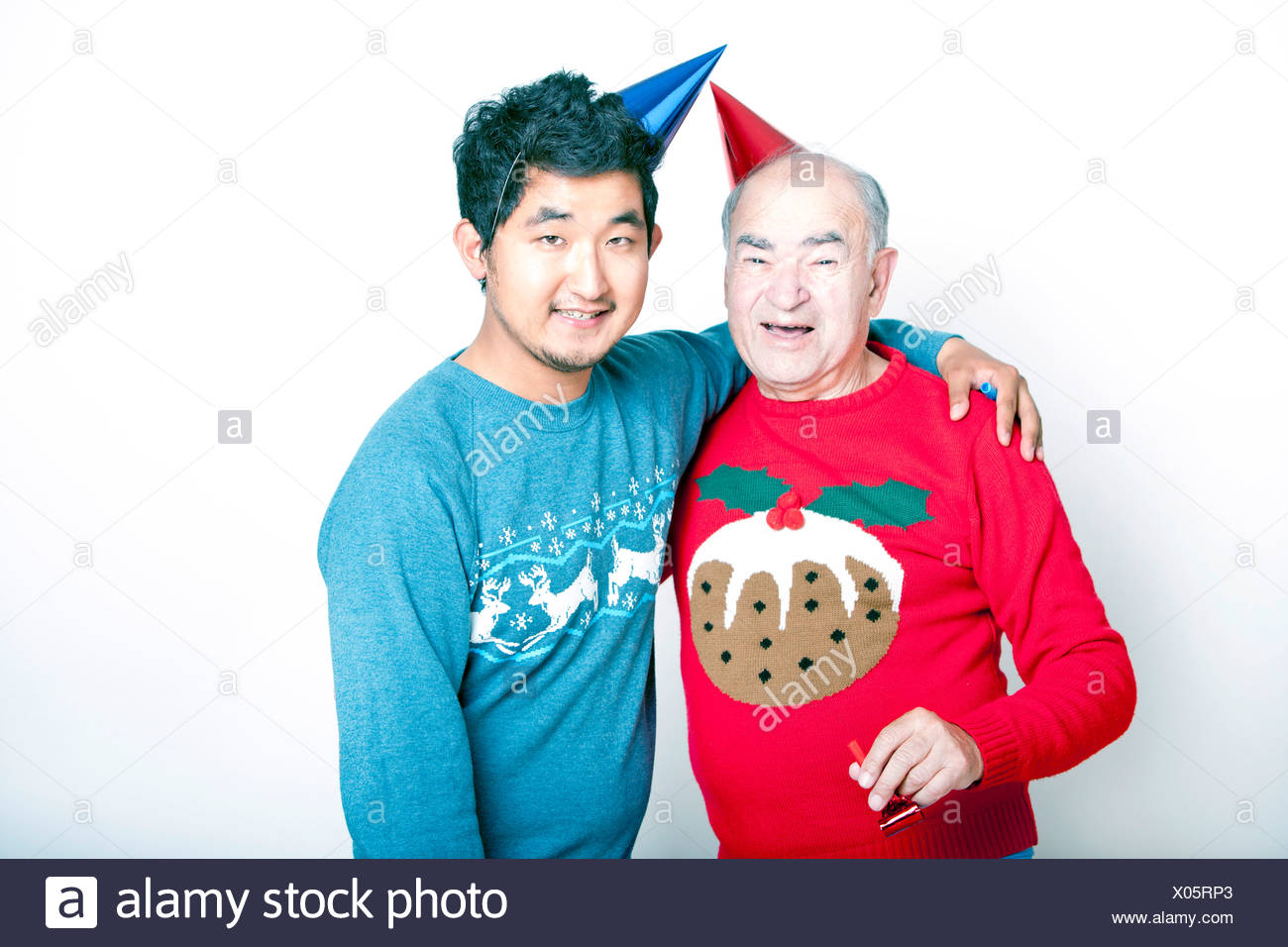 Portrait a Senior adult man a young Asian man wearing Christmas jumpers party hats - Stock Image