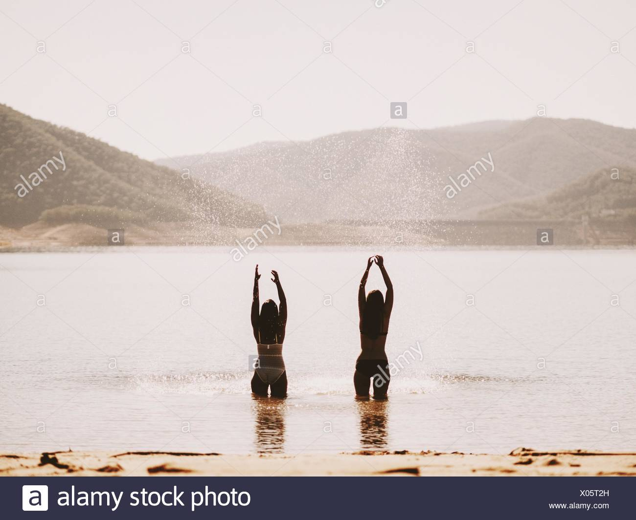 Rear View Of Friends With Arms Outstretched Standing On Beach By Mountains Against Clear Sky - Stock Image
