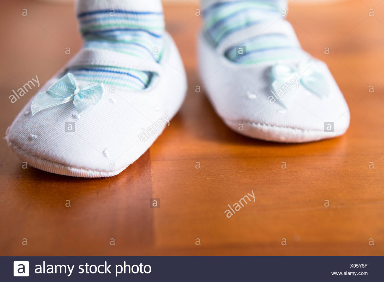 Baby in booties taking first step - Stock Image