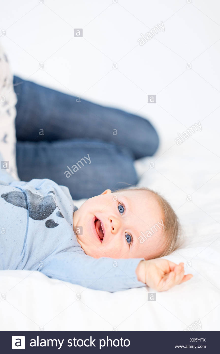 beautiful mother and baby boy sitting in childroom - Stock Image