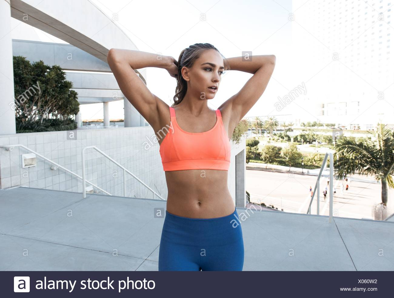 Young woman wearing sports bra, hands behind head, looking away - Stock Image