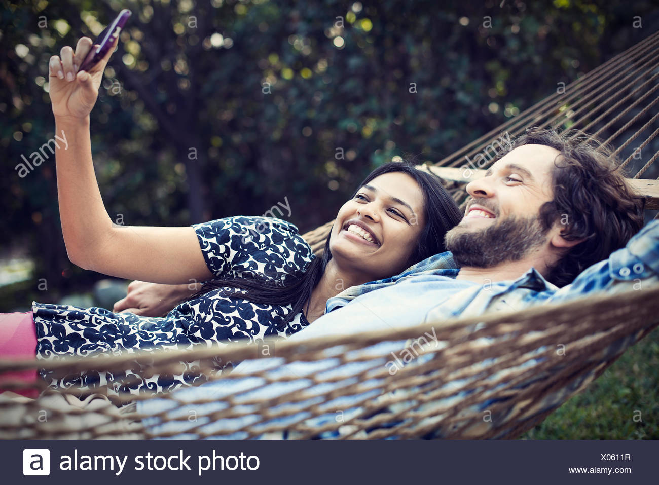 A couple, a young man and woman lying in a large hammock in the garden, taking a selfy of themselves. - Stock Image