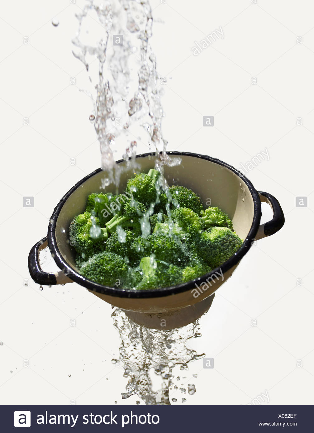 Water falling through colander with fresh broccoli - Stock Image