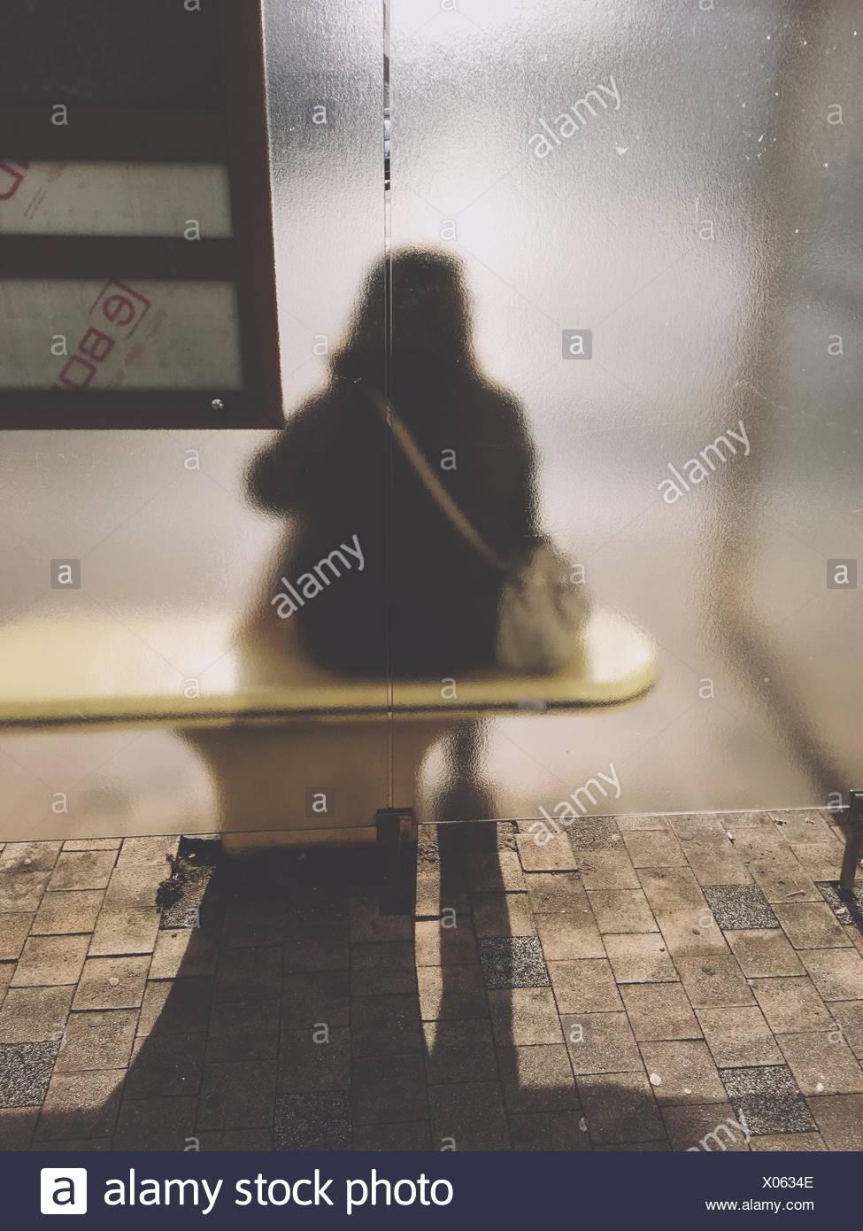 Rear View Of Person Sitting On Bench Seen Through Frosted Glass Window - Stock Image
