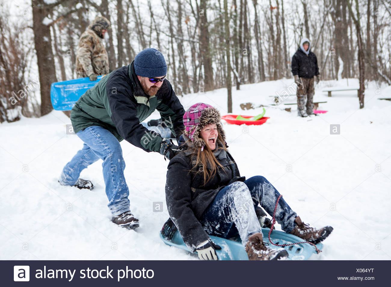 Mid adult couple and teenage son playing on toboggans - Stock Image