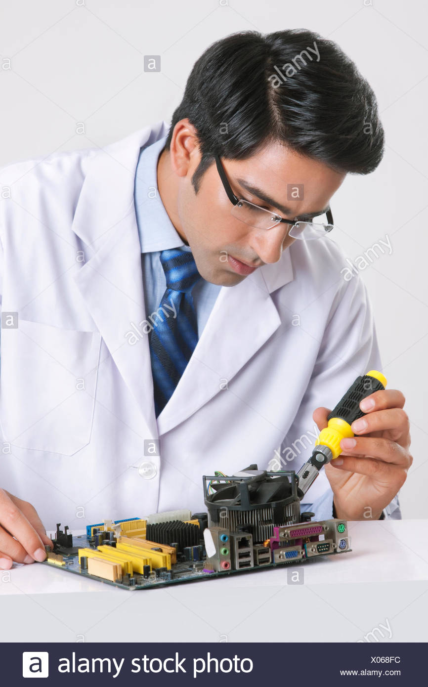 Young technician repairing machine part at table over gray background - Stock Image