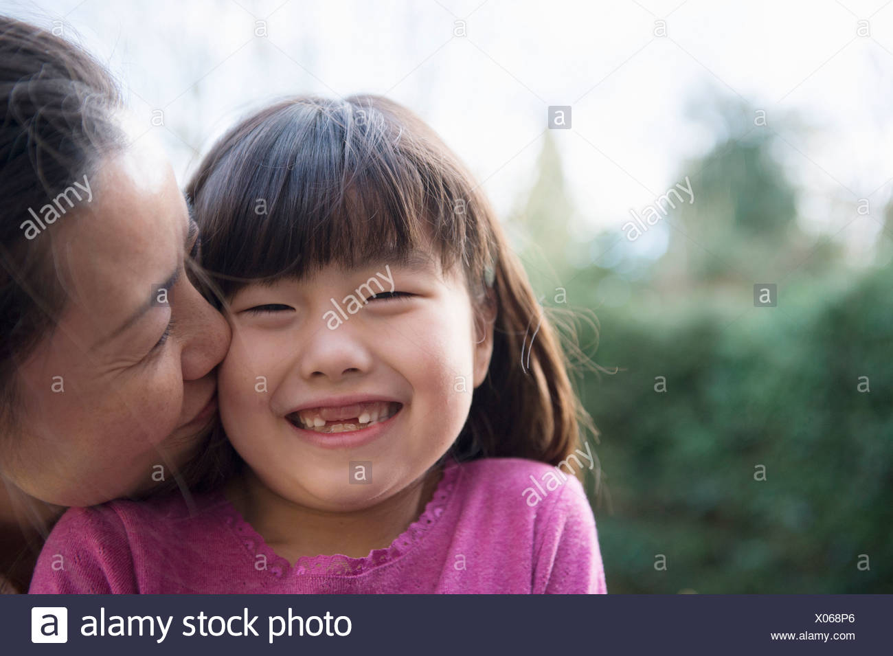 Girl being kissed on the cheek by her mother in the garden - Stock Image