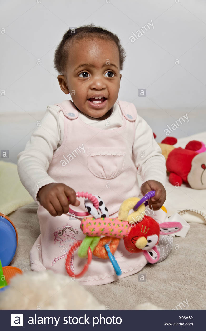 Black female baby playing with toys - Stock Image