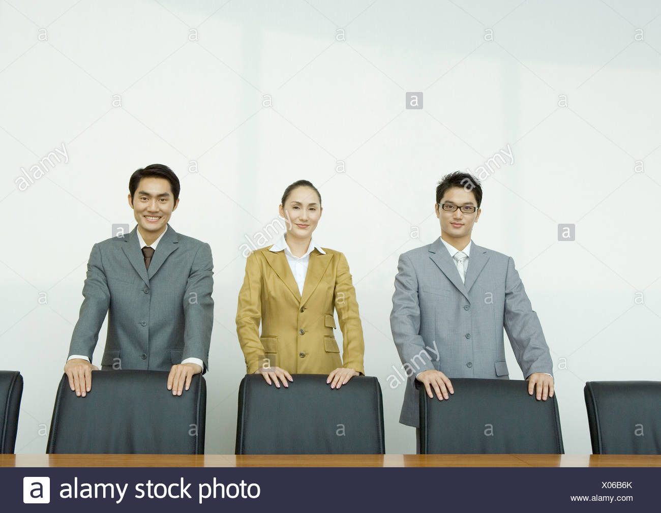 Business executives standing with hands on backs of chairs in conference room - Stock Image