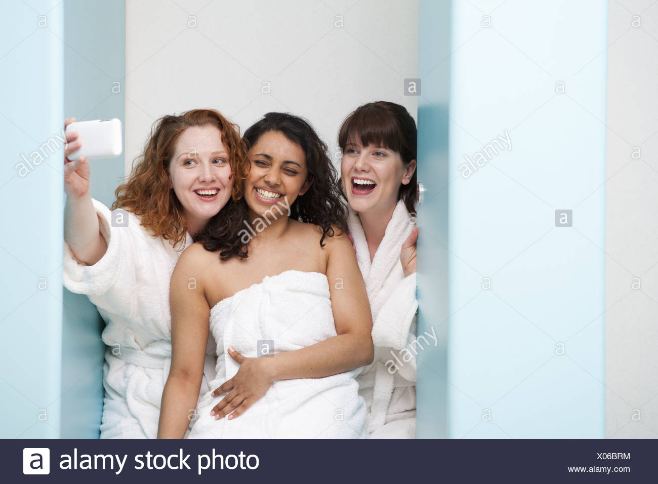 Women taking pictures in locker room - Stock Image