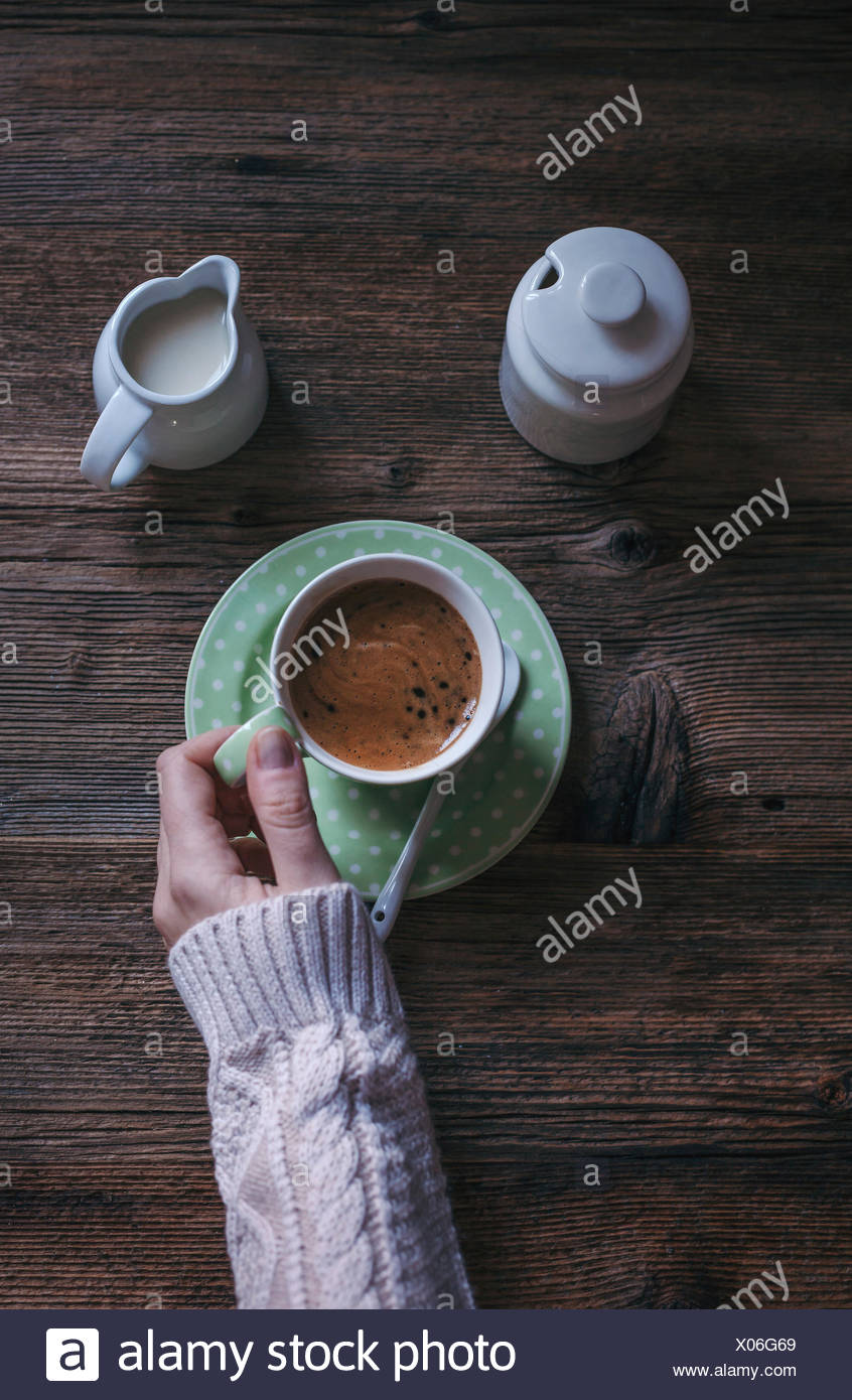 A womans hands holding a cup of strong black coffee, with milk and sugar. - Stock Image