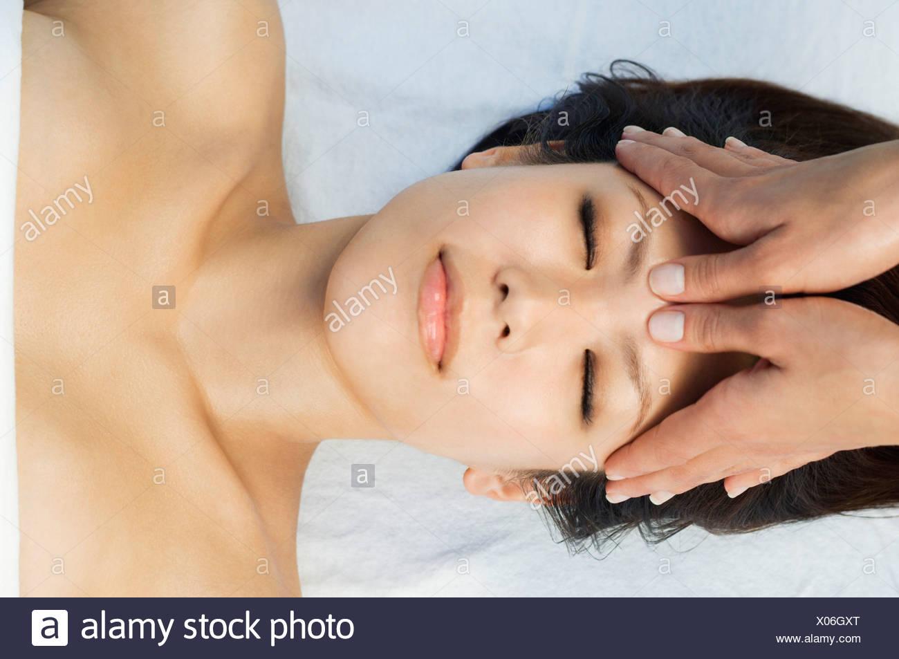 Young woman having head massage at health spa Stock Photo
