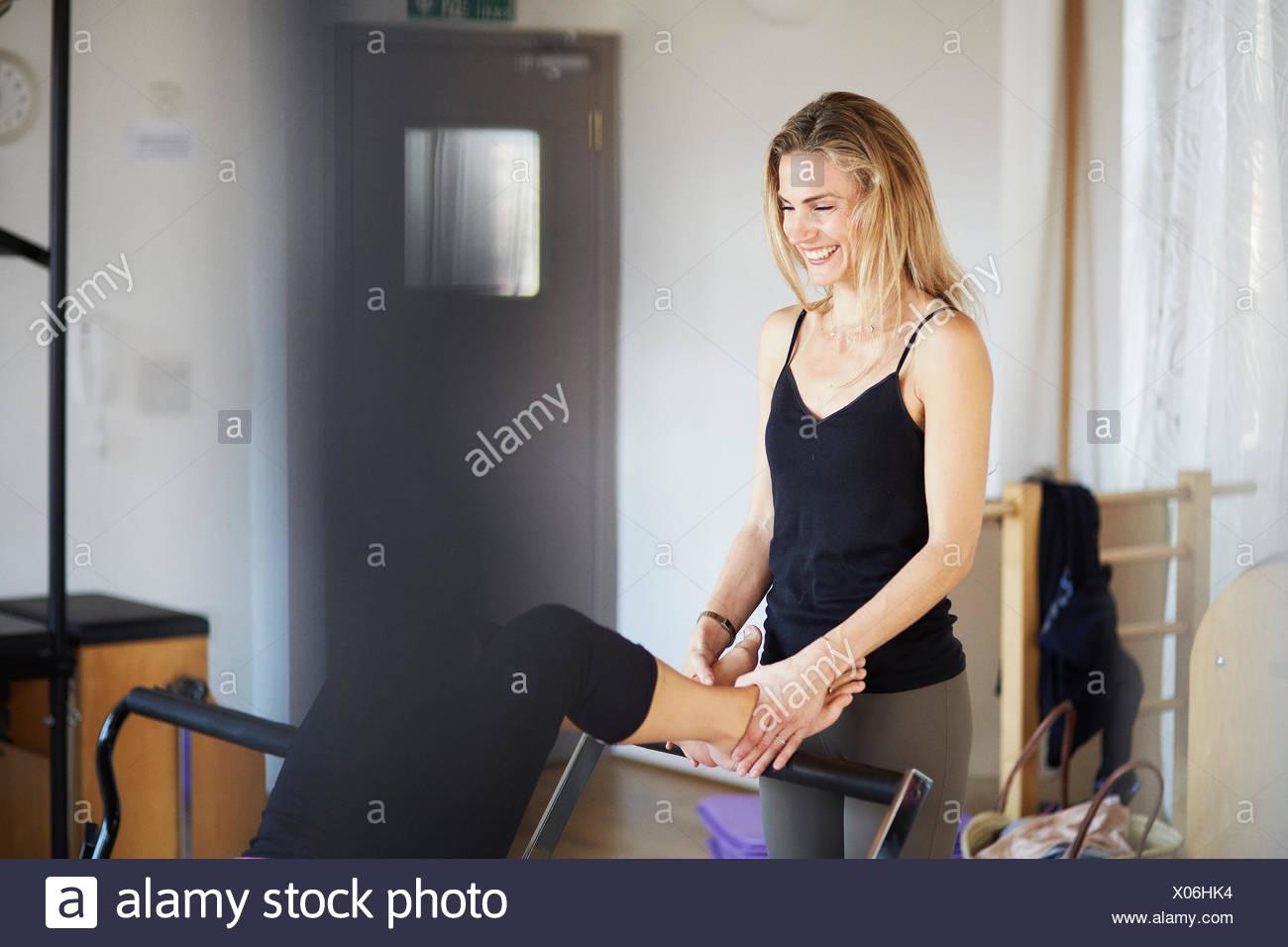 Teacher holding feet of female student lying on reformer in pilates gym - Stock Image
