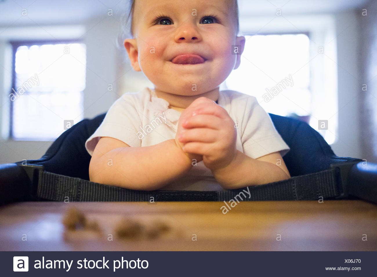 Toddler girl licking lips in highchair - Stock Image