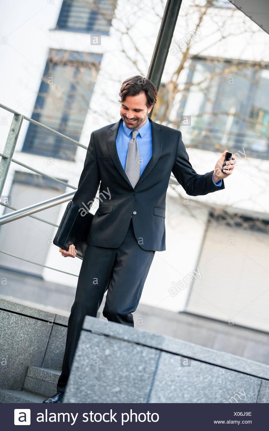 Fröhlicher erfolgreicher Geschäftsmann mit dunklem Anzug und dunklen Haaren freudig vor einem Geschäftsgebäude Stock Photo