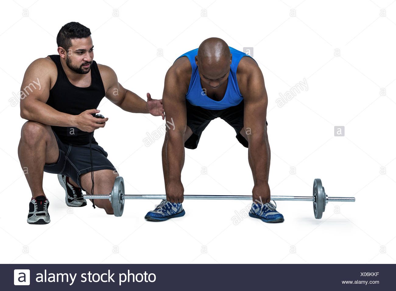 Man lifting barbell with trainer - Stock Image