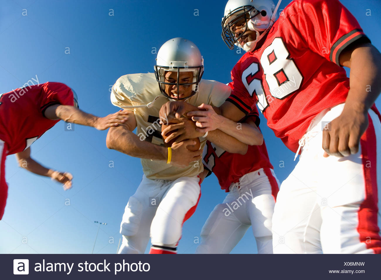 American football players tackling opposing player with ball, low angle view - Stock Image