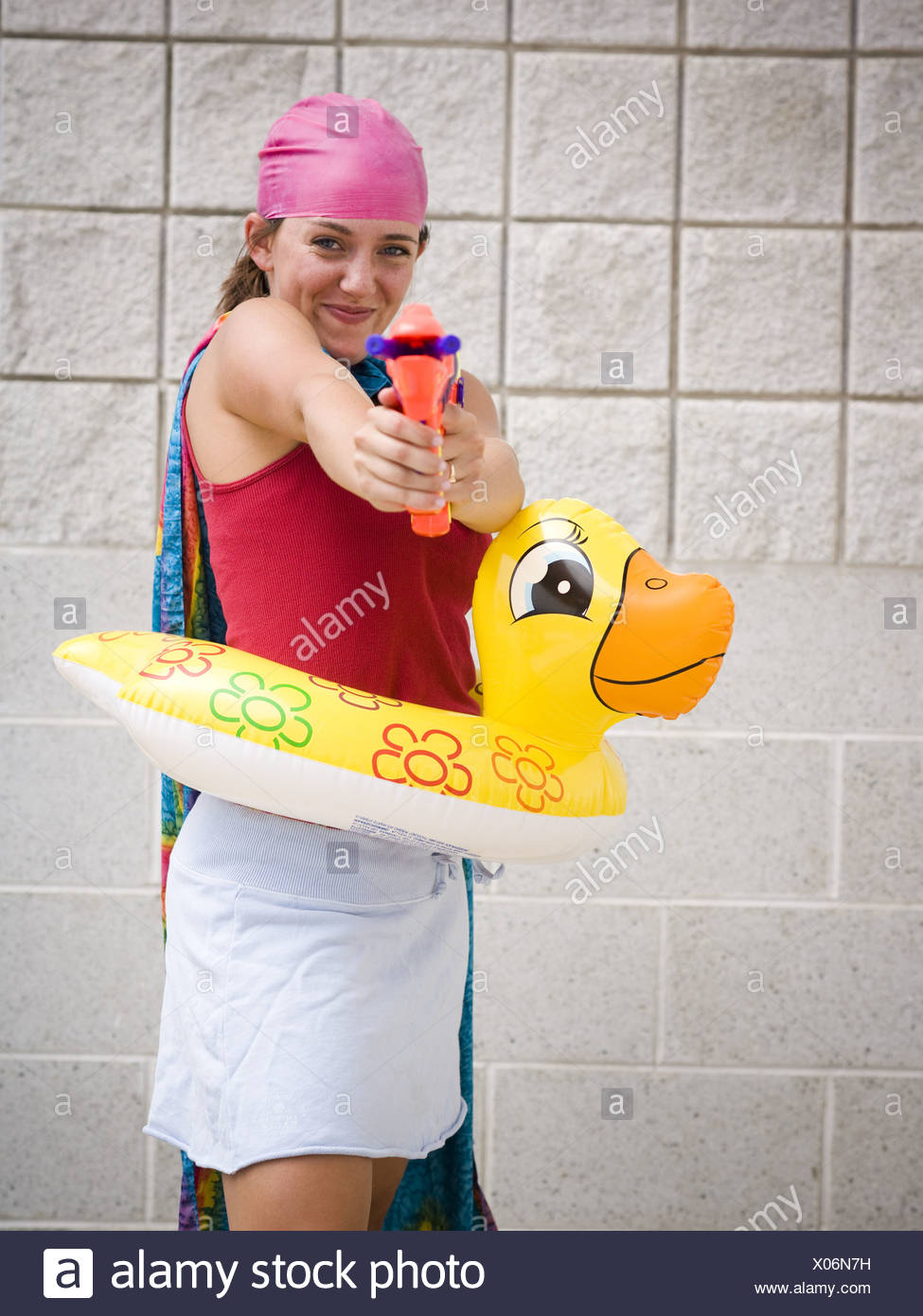 Girl at swimming pool with life ring and water pistol Stock Photo