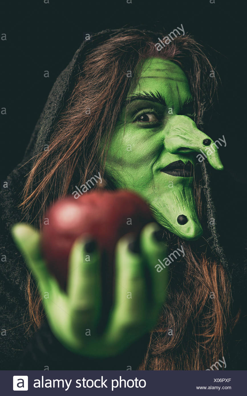 Evil witch holding a red apple - Stock Image