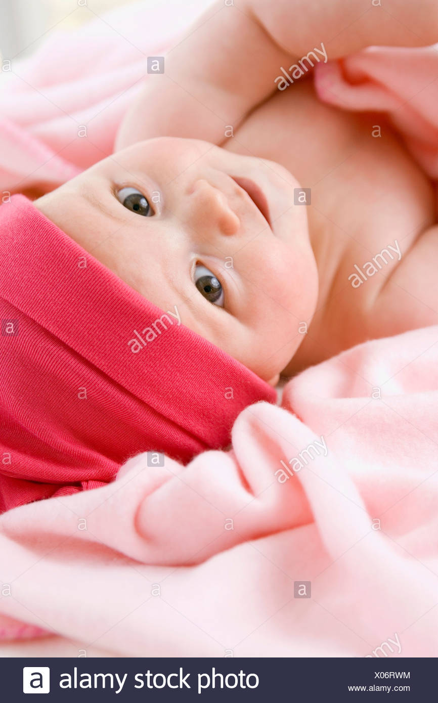 Baby girl (6-9 months) lying on back, portrait - Stock Image