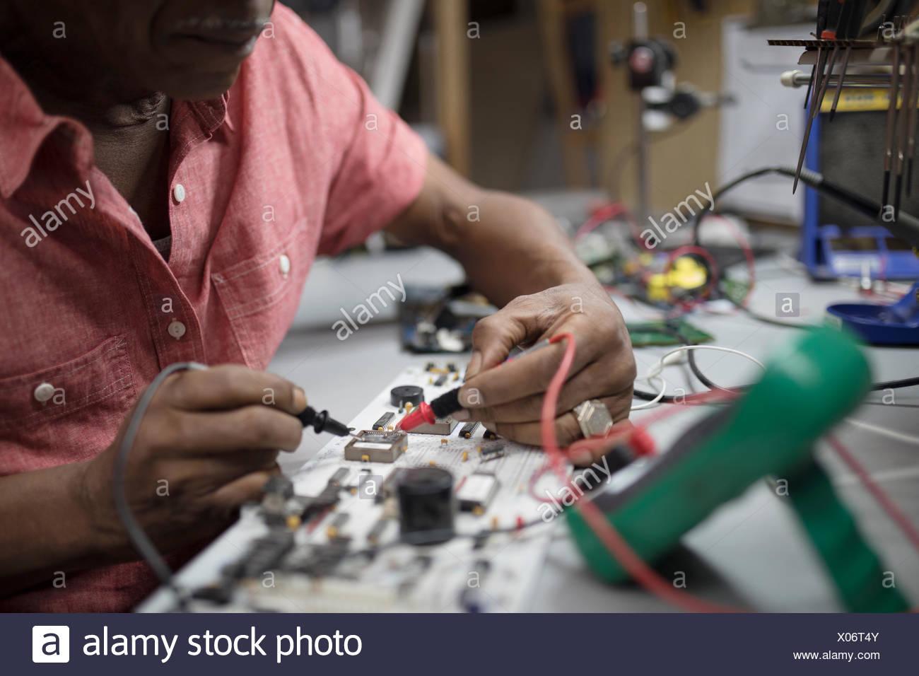 Close up male engineer using soldering iron on electronics - Stock Image