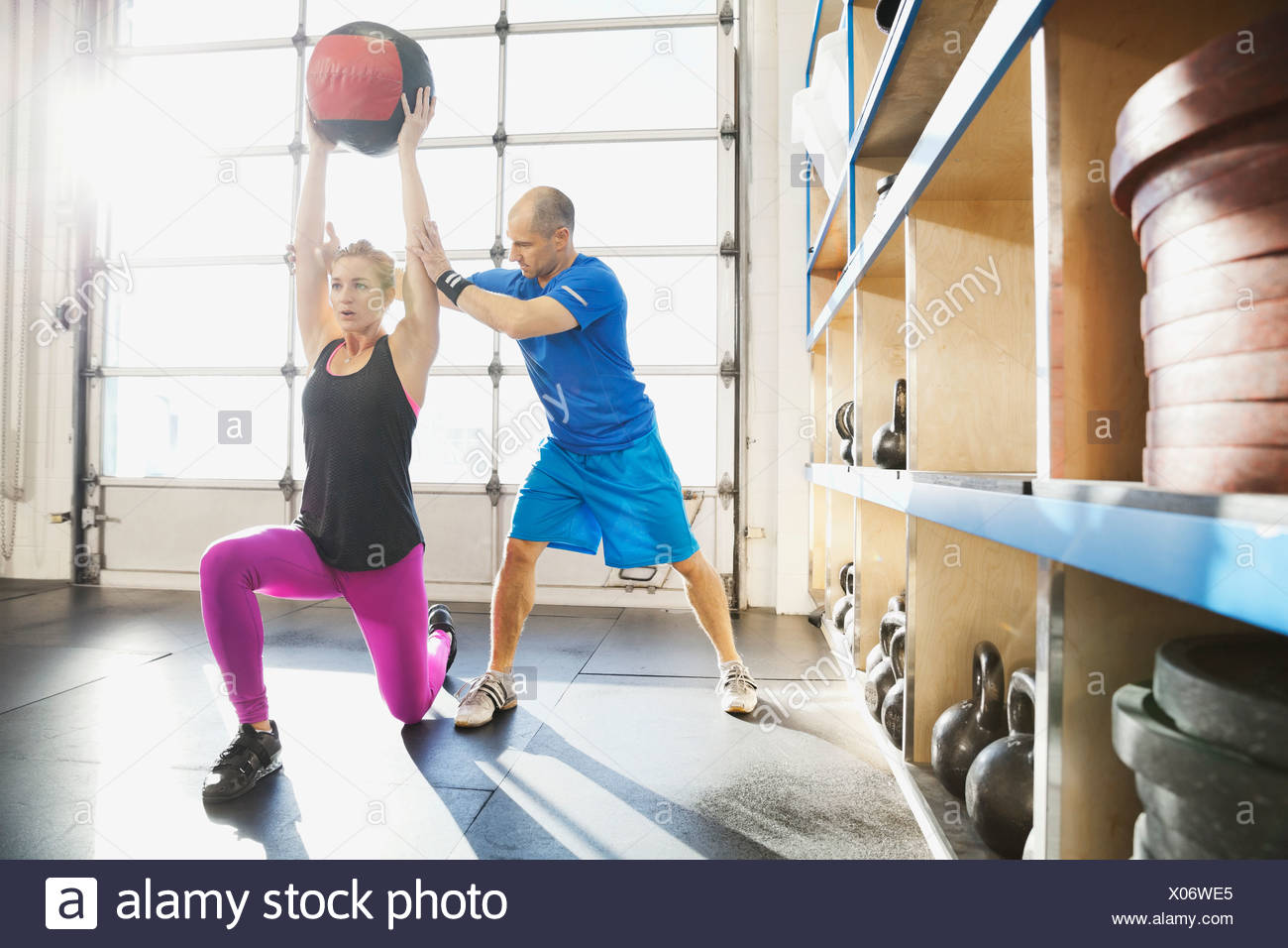 Gym instructor assisting woman with medicine ball lunge - Stock Image