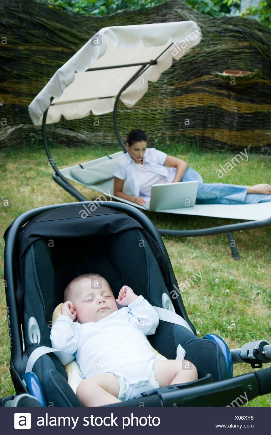 mother working on laptop while baby's sleeping in garden Stock Photo
