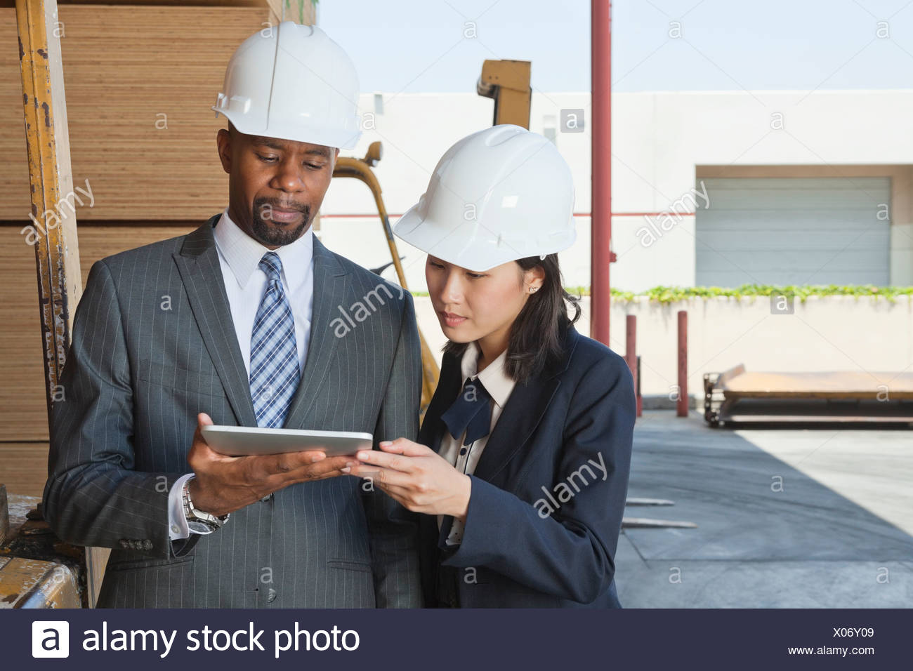 Multiethnic contractors using tablet PC at timber yard - Stock Image