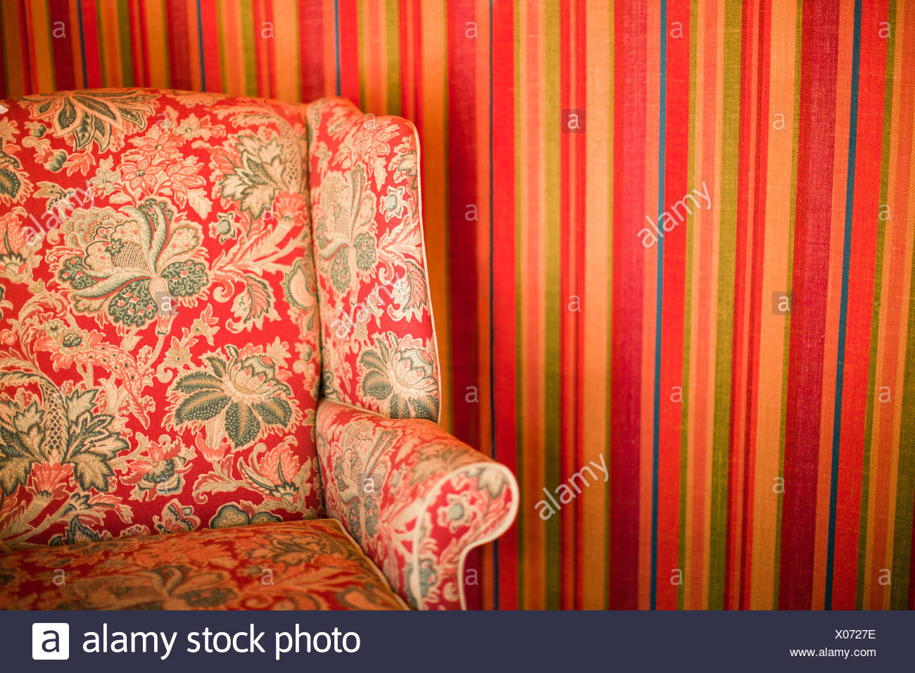 Floral patterned chair against striped wall - Stock Image