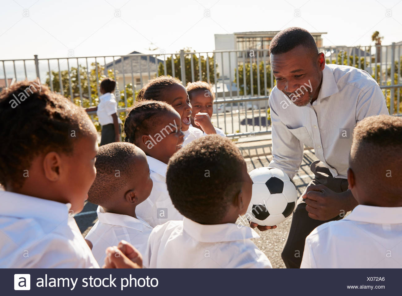 Young kids in a school playground with teacher holding ball - Stock Image
