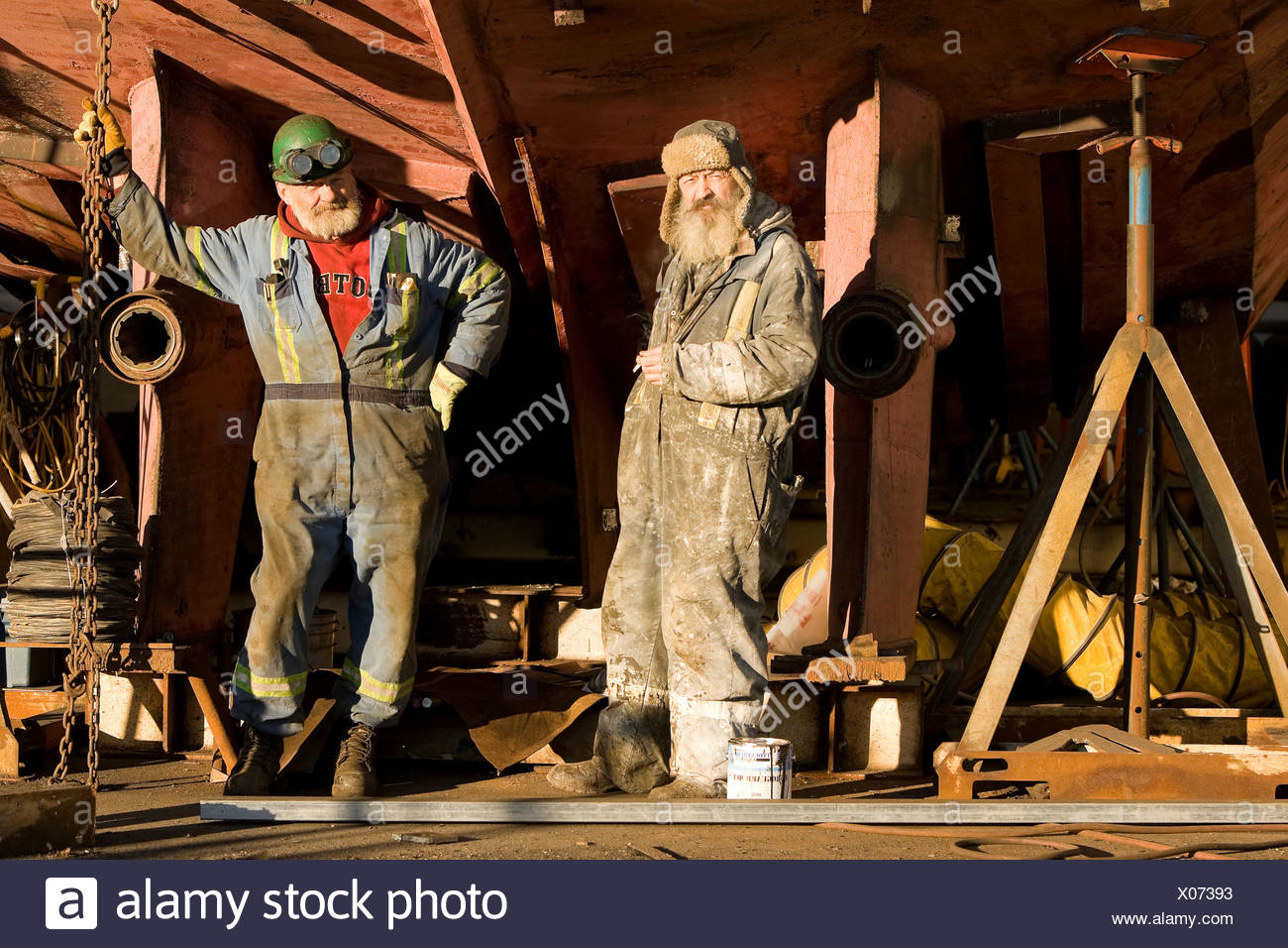 Welder and ship-painter relax during a break while refitting a tugboat at a shipyard in Campbell River.  Vancouver Island Britis - Stock Image
