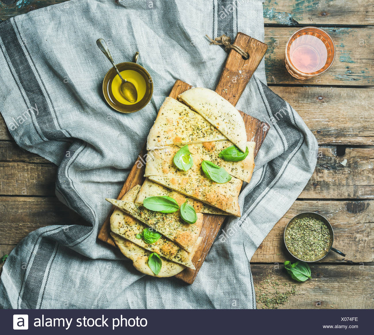 Homemade Italian focaccia flatbread cut into pieces with herbs, fresh basil leaves, olive oil and glass of rose wine on rustic s - Stock Image