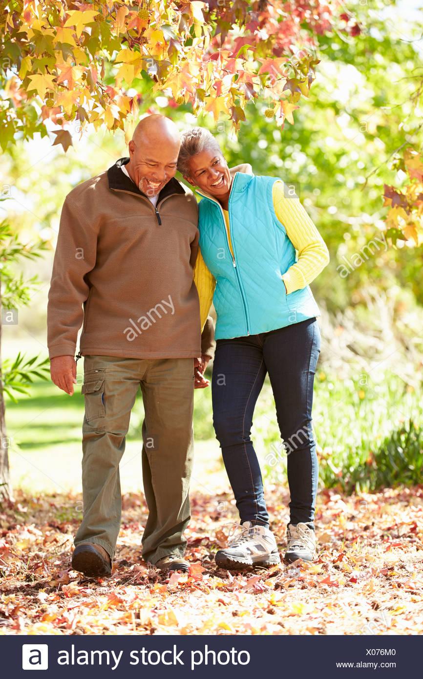 Senior Couple Walking Through Autumn Woodland - Stock Image