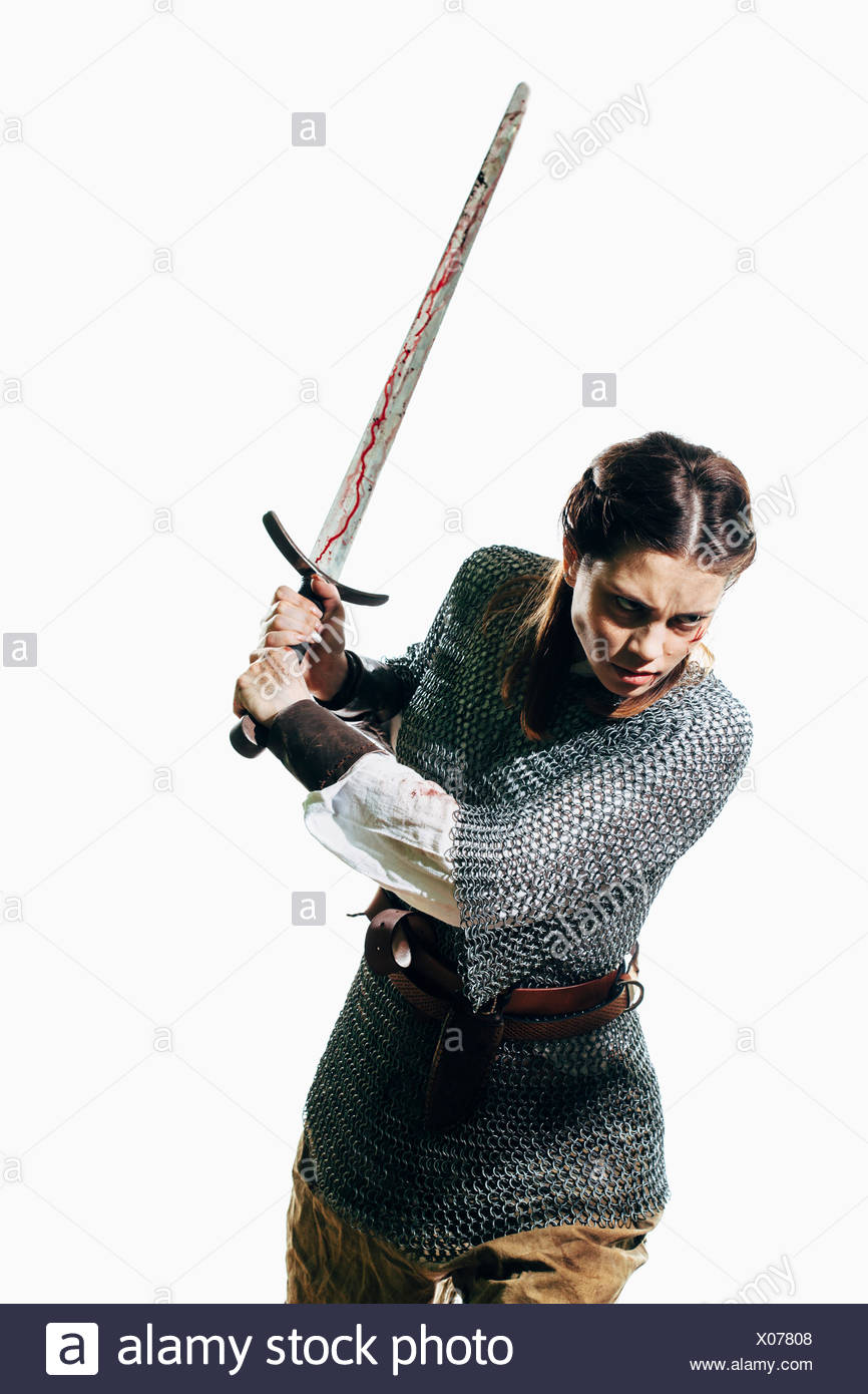 Angry woman wearing chain mail holding sword against white background - Stock Image