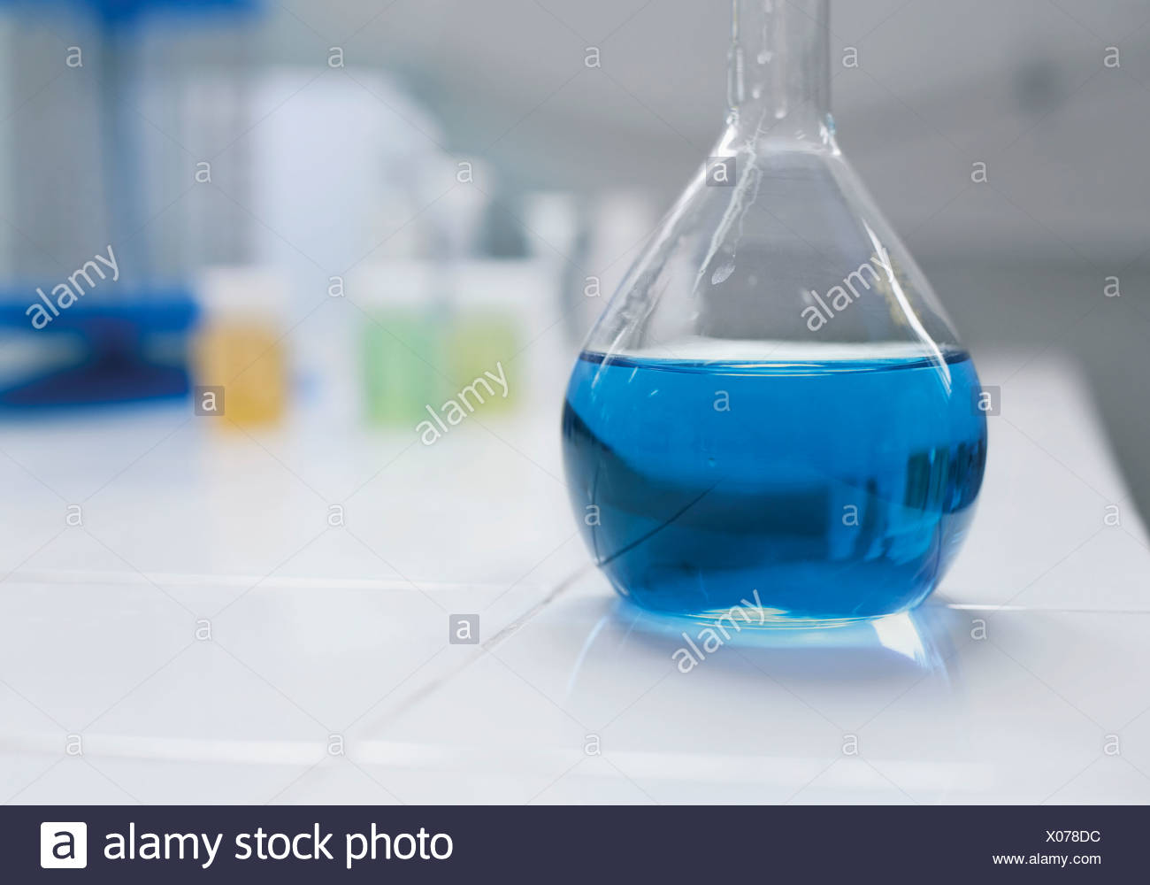Glass flask with blue fluid, close up - Stock Image