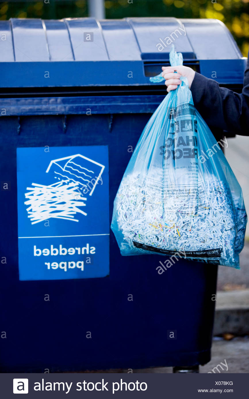 A businessman recycling a bag of shredded paper - Stock Image