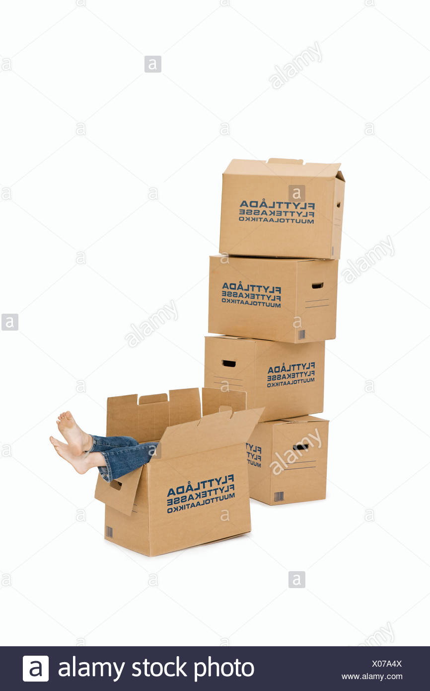 A girl sitting in a box. - Stock Image