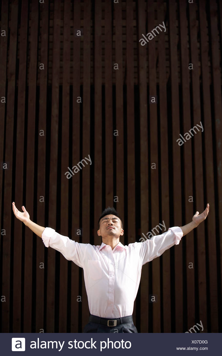 Man Standing Outdoors In Meditation Pose - Stock Image