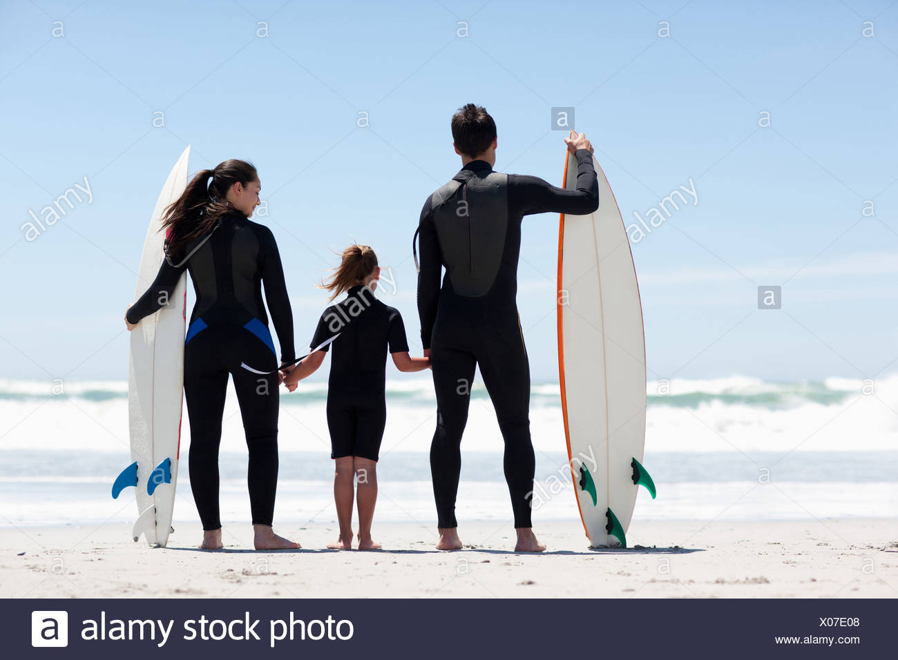 Family in wetsuits with surfboards holding hands on beach - Stock Image