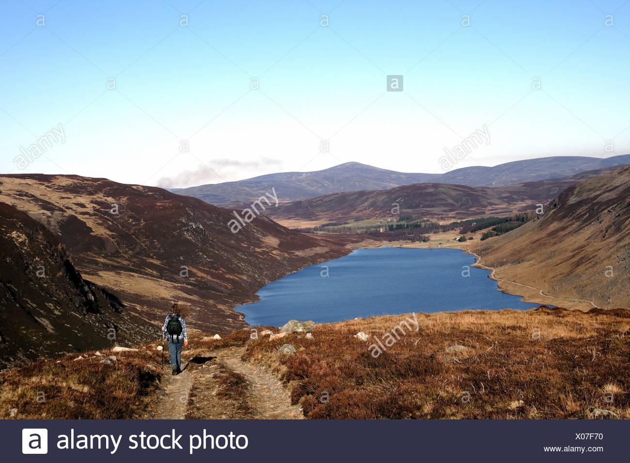 Hillwalker descending to Loch Lee. - Stock Image