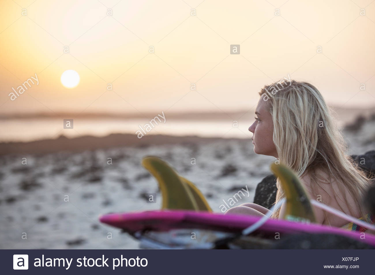 Blonde surfer girl sitting on the beach at sunset - Stock Image