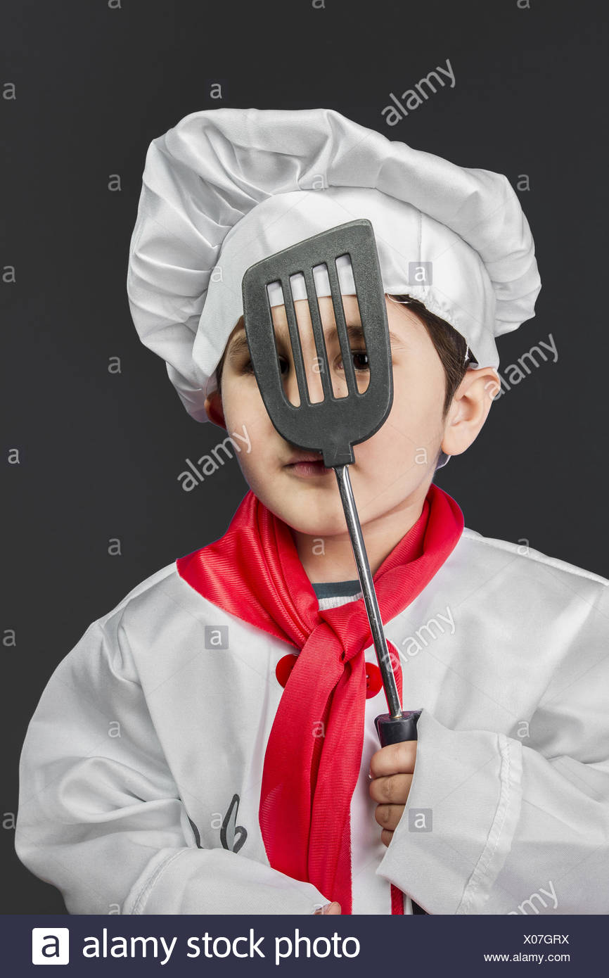 Cooking, Little boy preparing healthy food on kitchen over grey background, cook hat - Stock Image
